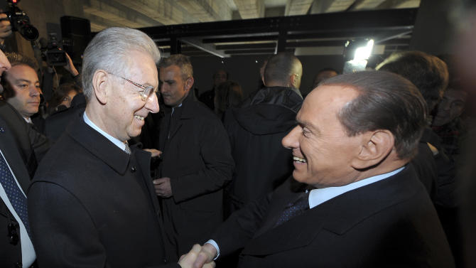 Italian Premier Mario Monti, left, and former Premier Silvio Berlusconi shake hands in Milan, Italy, Sunday, Jan. 27, 2013. (AP Photo/Antonio Calanni)