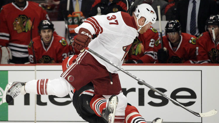 CORRECTS HOSSA FROM SLOVAKIA, NOT RUSSIA - Chicago Blackhawks' Marian Hossa (81) of Slovakia, falls down after  taking a hit from Phoenix Coyotes' Raffi Torres (37) during the first period of Game 3 of an NHL hockey Stanley Cup first-round playoff series in Chicago, Tuesday, April 17, 2012. (AP Photo/Nam Y. Huh)