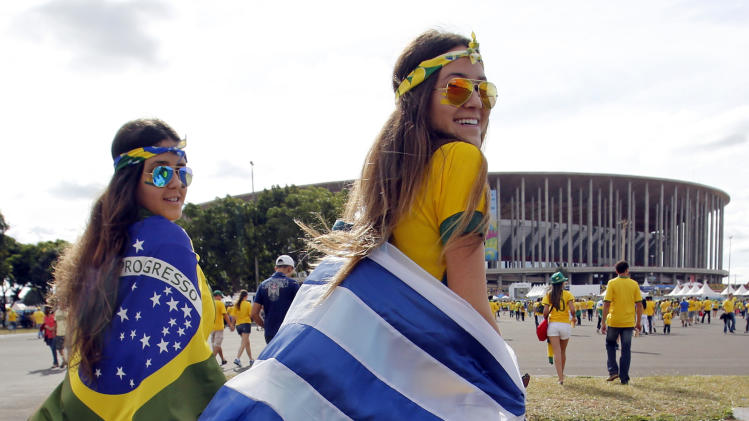 Soccer fans arrive for the group A World Cup soccer match between Cameroon and Brazil at the Estadio Nacional in Brasilia, Brazil, Monday, June 23, 2014