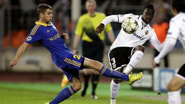 BATE Borisov's Dmitri Likhtarovich (L) fights for the ball with Valencia's Aly Cissokho during their Champions League Group F match