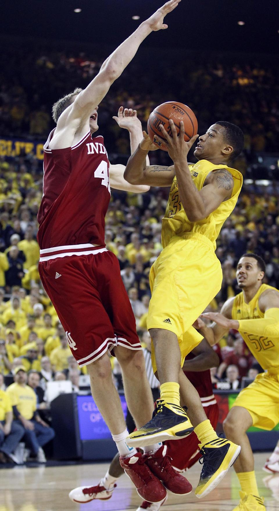Indiana forward Cody Zeller (40) defends against the last shot of the game by Michigan guard Trey Burke (3) in an NCAA college basketball game Sunday, March 10, 2013, in Ann Arbor, Mich. Burke missed the shot to give Indiana a 72-71 win. (AP Photo/Duane Burleson)