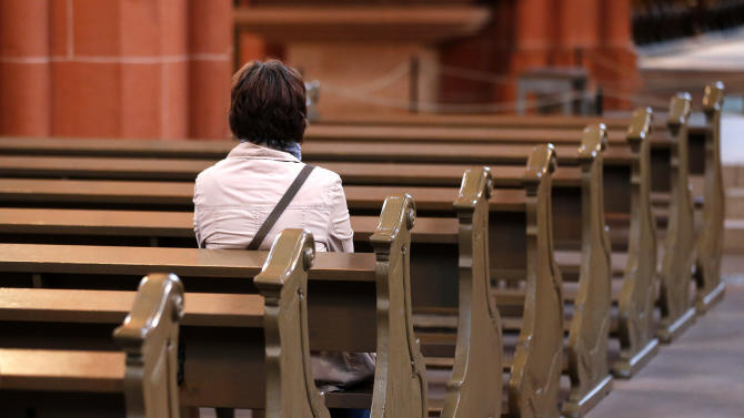 In this photo taken on Thursday, Sept. 27, 2012, a woman sits on a bench in the cathedral of Frankfurt, Germany.  The road to heaven is paved with more than good intentions for Germany's 24 million Catholics. If they don't pay their religious taxes, they will be denied sacraments, including weddings, baptisms and funerals.  A decree issued last week by the country's bishops cast a spotlight on the longstanding practice in Germany and a handful of other European countries in which governments tax registered believers and then hand over the money to the religious institutions.  (AP Photo/Michael Probst)