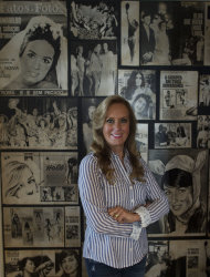 "In this July 3, 2012 photo, Heloisa ""Helo"" Pinheiro, the woman that inspired the classic bossa nova song, ""The Girl From Ipanema,"" poses for a photo backdropped by a collage of pictures from her youth, in Sao Paulo, Brazil. The quintessential tune was inspired by Pinheiro when she passed the songwriters in a beach side bar on her way to the sea, 50 years ago. To its legions of fans, the decades have only heightened the song's allure, adding a wash of nostalgia to this hymn to passing youth and beauty. At 68, Pinheiro has two TV shows roles and is planning to launch a book in English about her past. (AP Photo/Andre Penner)"