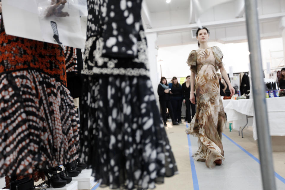 A model practices walking in her outfit before the Rodarte fall 2012 collection show during Fashion Week, Tuesday, Feb. 14, 2012, in New York. (AP Photo/Jason DeCrow)