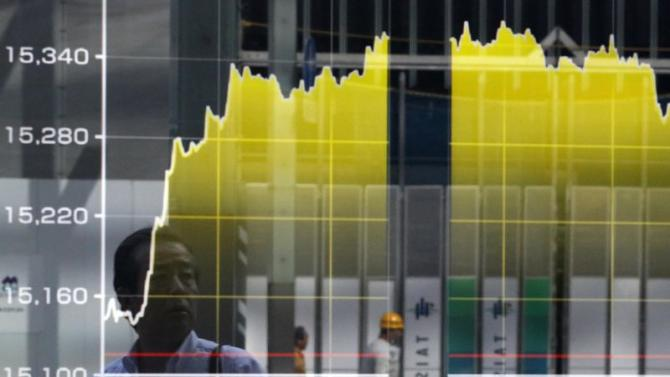 A pedestrian is reflected on an electronic board showing the graph of the recent fluctuations of Japan's Nikkei average outside a brokerage in Tokyo