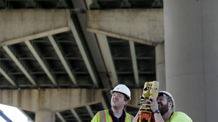 Surveyors work below the Interstate 495 bridge