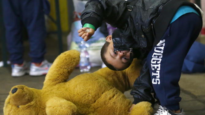 Young boy plays with a teddy bear he received at registration point for migrant arrivals in Munich