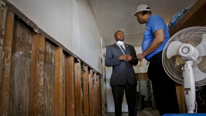 In this May 7, 2013 photo, Gregory Hylton, right, speaks with Councilman Donovan Richards while taking him on tour of his basement, in New York.  Hylton's basement is covered in mold, a development he says resulted in the aftermath of Sandy storm damage. Seven months after Superstorm Sandy, the Red Cross still hasn't spent more than a third of the $303 million it raised to assist victims of the storm, a strategy the organization says will help address needs that weren't immediately apparent in the disaster's wake. (AP Photo/Bebeto Matthews)