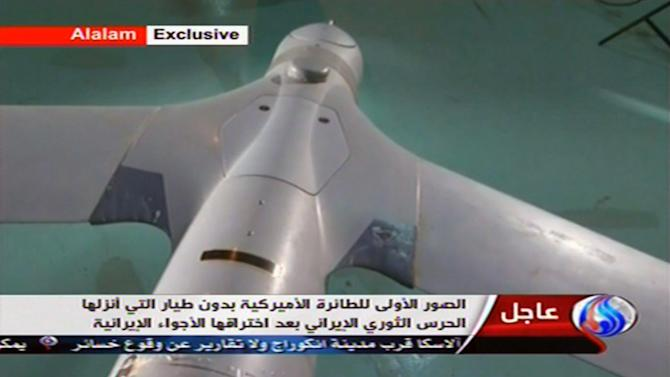 "In this image taken from the Iranian state TV's Arabic-language channel Al-Alam, showed what they purport to be an intact ScanEagle drone aircraft put on display, as an exclusive broadcast Tuesday Dec. 4, 2012, showing what they say are the first pictures of a captured drone.  Iran authorities claimed Tuesday it had captured a U.S. drone after it entered Iranian airspace over the Persian Gulf,  and showing an image of a purportedly downed craft on state TV,  but the U.S. Navy said all its unmanned aircraft in the region were ""fully accounted for.""(AP Photo / Al-Alam TV)  TV OUT"
