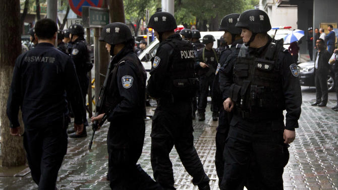 In this May 22, 2014 photo, armed policemen prepare to patrol near the site of the explosion in Urumqi, northwest China's Xinjiang Uygur Autonomous Region. So far this month, police in China's restive western region of Xinjiang have broken up 23 terror and religious extremism groups and caught over 200 suspects, state media reported Monday, May 26. (AP Photo/Andy Wong)