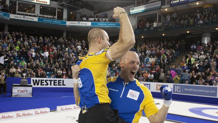 Team Alberta lead Nolan Thiessen lifts up third Pat Simmons after winning their 2014 Tim Hortons Brier curling championships against team British Columbia in Kamloops