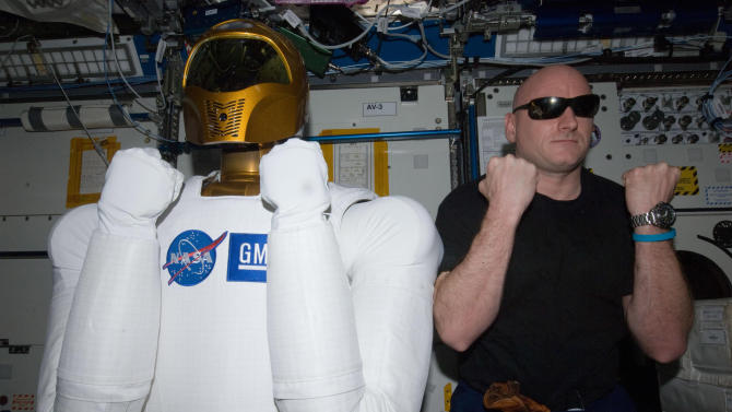 FILE - In this March 15, 2011 file photo provided by NASA, astronaut Scott Kelly, Expedition 26 commander, right, poses with Robonaut 2, the dexterous humanoid astronaut helper, in the Destiny laboratory of the International Space Station. NASA ground controllers on Monday, Aug. 22, 2011 turned on the robot for the first time since it was delivered to the International Space Station in February. (AP Photo/NASA)