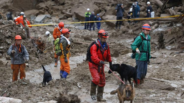 Rescue workers search for survivors with rescue dogs at a site where a landslide swept through a residential area at Asaminami ward in Hiroshima