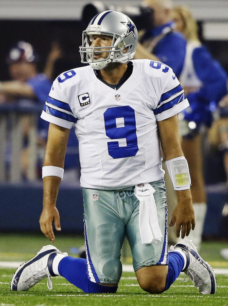 Dallas Cowboys quarterback Tony Romo kneels on the field after throwing an interception to New York Giants safety Ryan Mundy (21) during the first half of an NFL football game, Sunday, Sept. 8, 2013, in Arlington, Texas. (AP Photo/Tony Gutierrez)