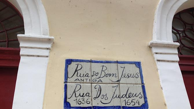 In this June 24, 2014 photo, a street sign for Rua do Bom Jesus decorates the side of a Jewish memorial and cultural center in Recife, Brazil. The building sits upon the ruins of what is widely accepted to have been the first synagogue built in the Americas. Recife was initially settled by the Portuguese in the 1530s, but the Dutch invaded in 1630 and ruled the region for 24 years. It was during this period that Jews who had previous settled in Amsterdam, many of them of Portuguese descent, began moving to Recife for business and religious purposes. (AP Photo/Brett Martel)