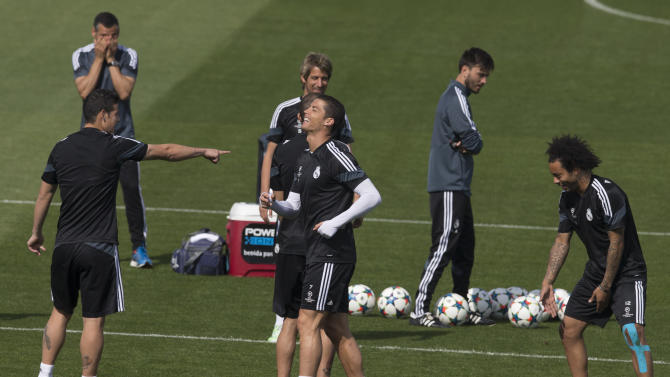 Real Madrid's Cristiano Ronaldo, centre, smiles during a training session in Madrid, Spain Tuesday April 21, 2015. Real Madrid will play Atletico Madrid Wednesday in a Champions League quarterfinal second leg soccer match in Madrid.(AP Photo/Paul White)