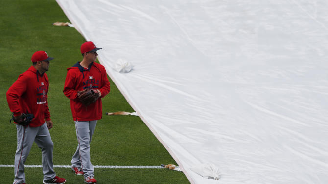 Members of the Los Angeles Angels walk past the tarpaulin as it covers the diamond from a light rain in Coors Field before they face the Colorado Rockies in the first inning of an inter league baseball game Tuesday, July 7, 2015, in Denver. (AP Photo/David Zalubowski)