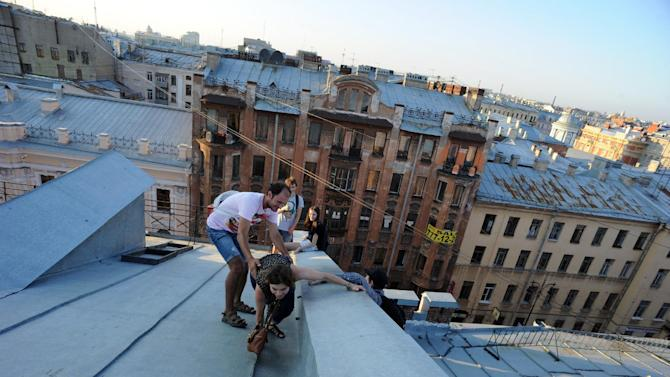 Climbers reach the top of a roof in the center of the Russian city of Saint Petersburg, on August 6, 2014
