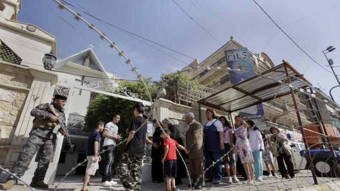 Iraqi Christians are searched as they queue up to attend Easter at Virgin Mary Chaldean Church in Baghdad, Iraq, Sunday, April 24, 2011. The Chaldean Church is an Eastern Rite church affiliated with the Roman Catholic Church. (AP Photo/Khalid Mohammed)