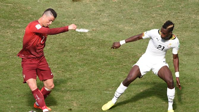 Portugal's forward and captain Cristiano Ronaldo (L) and Ghana's defender John Boye vie for the ball at the Mane Garrincha National Stadium in Brasilia during the 2014 FIFA World Cup on June 26, 2014