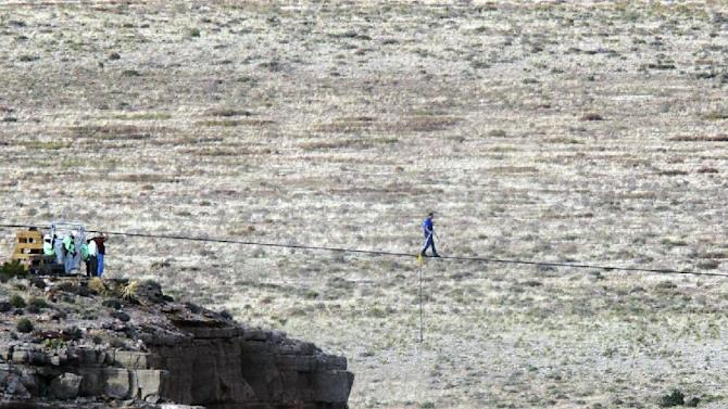 Daredevil Nik Wallenda crosses a tightrope 1,500 feet above the Little Colorado River Gorge, Ariz., on Sunday, June 23, 2013, on the Navajo Nation outside the boundaries of Grand Canyon National Park. Wallenda completed the tightrope walk that took him a quarter mile over the gorge in just more than 22 minutes. (AP Photo/Rick Bowmer)