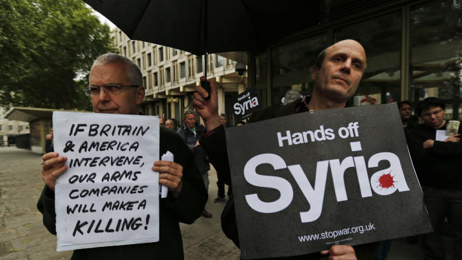 Protesters hold placards as they demonstrate against western intervention in Syria, outside the US embassy in central London, Saturday, June 15, 2013. (AP Photo/Lefteris Pitarakis)