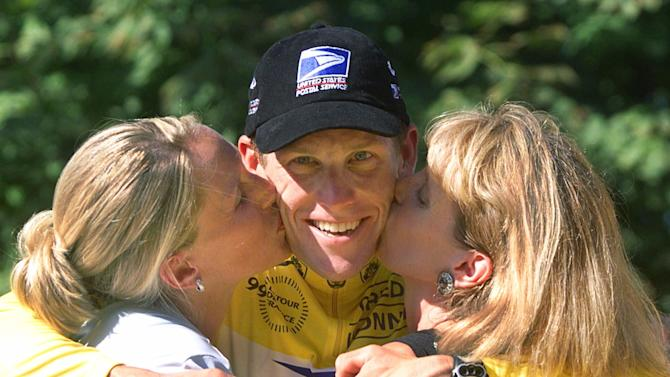 FILE - This July 25, 1999 file photo shows Tour de France winner Lance Armstrong being kissed by his wife Kristin, left, and his mother Linda after the 20th and final stage of the Tour de France cycling race in Paris. The superstar cyclist, whose stirring victories after his comeback from cancer helped him transcend sports, chose not to pursue arbitration in the drug case brought against him by the U.S. Anti-Doping Agency. That was his last option in his bitter fight with USADA and his decision set the stage for the titles to be stripped and his name to be all but wiped from the record books of the sport he once ruled.  (AP Photo/Laurent Rebours, File)