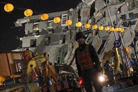 Soldiers stand guard in front of 17-storey apartment building collapsed after an earthquake, on the first day of the Chinese Lunar New Year at Tainan, southern Taiwan