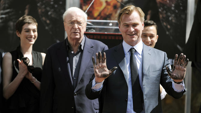 """Christopher Nolan, director of the upcoming film """"The Dark Knight Rises,"""" holds up his hands after putting them in cement during a ceremony for him at Grauman's Chinese Theatre on Saturday, July 7, 2012, in Los Angeles. Looking on from left are cast members Anne Hathaway, Michael Caine and Joseph Gordon-Levitt. (Photo by Chris Pizzello/Invision/AP)"""