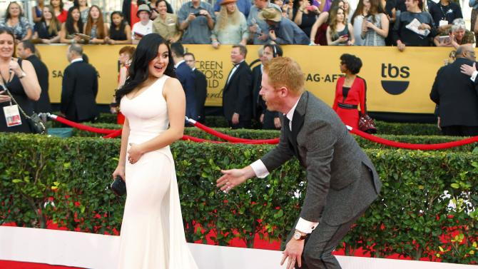 "Actress Ariel Winter of NBC's ""Modern Family,"" has her dress adjusted by co-star Jesse Tyler Ferguson at the 21st annual Screen Actors Guild Awards in Los Angeles"