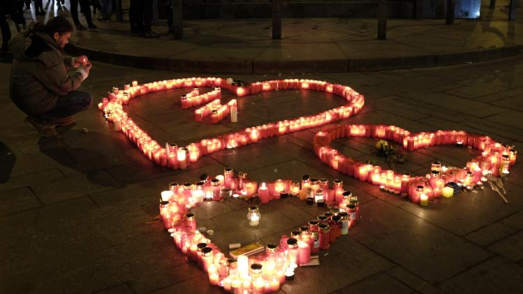 A man places a candle as he pays his respects to former Czech President Vaclav Havel at Wenceslas Square in Prague