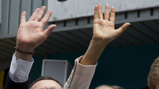 Marina Silva, presidential candidate of the Brazilian Socialist Party, PSB, right, and her running-mate Beto Albuquerque wave to supporters as they campaign in the Paraisopolis slum in Sao Paulo, Brazil, Wednesday, Oct. 1, 2014. Brazil will hold general elections on Oct. 5. (AP Photo/Andre Penner)