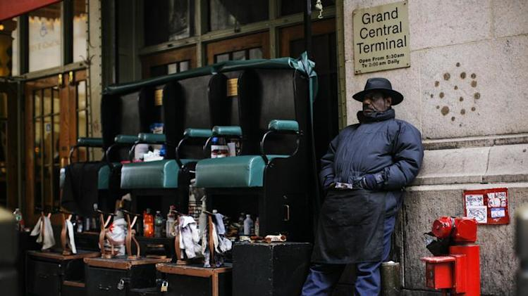 A worker waits for customers to shine shoes and boots at the entrance of Grand Central Station in New York