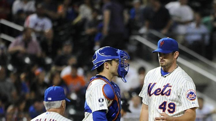 New York Mets catcher Travis d'Arnaud watches as New York Mets manager Terry Collins (10) takes starting pitcher Jonathon Niese (49) out of the game after the Atlanta Braves score two runs in the eighth inning of a baseball game at Citi Field on Thursday, Aug. 28, 2014, in New York. (AP Photo/Kathy Kmonicek)