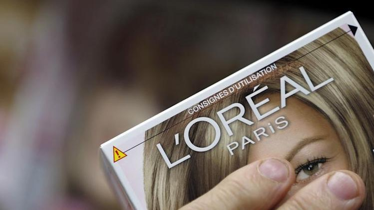 A customer holds a L'Oreal cosmetics group product in an supermarket in Lanton