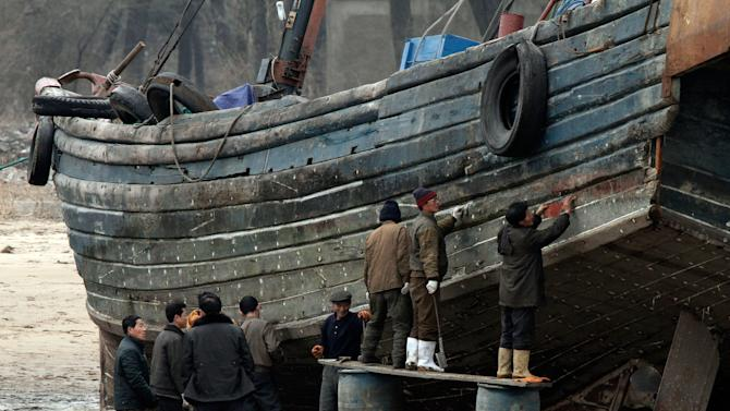 In this Wednesday March 6, 2013 photo, North Koreans repair a boat along the river bank of the North Korean town of Sinuiju, opposite side of the Chinese border city of Dandong. The U.N. Security Council responded swiftly to North Korea's latest nuclear test by punishing the reclusive regime Thursday with tough, new sanctions targeting its economy and leadership, despite Pyongyang's threat of a pre-emptive nuclear strike on the United States. (AP Photo) CHINA OUT