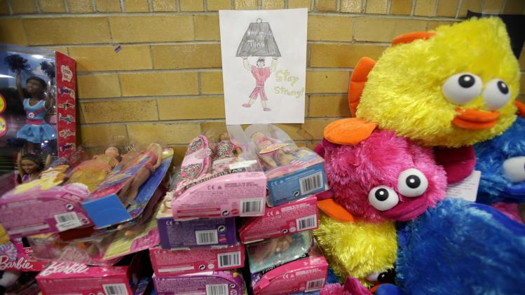A message of support hangs over a table full of donated toys at the town hall in Newtown, Conn., Friday, Dec. 21, 2012.   (AP Photo/Seth Wenig)