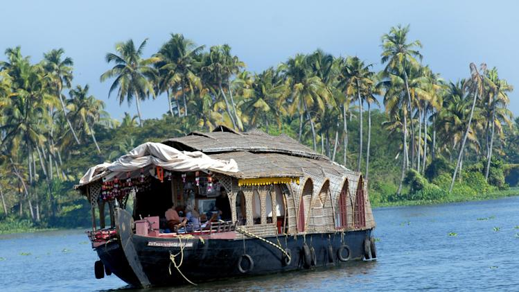 Tourists are seen enjoying a ride aboard a houseboat in the backwaters of Alappuzha, some 150 kms north of Thiruvananthapuram, capital of India's southern state of Kerala, on December 29, 2006