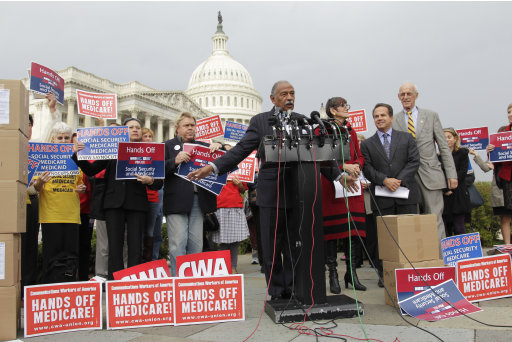 Rep. John Conyers, D-Mich., center, accompanied by fellow members of Congressm participate in an event on Capitol Hill in Washington, Wednesday, Oct. 26, 2011, to voice opposition to potential cuts in Medicare, Medicaid, and Social Security benefits as the deficit supercommittee looks for ways to reduce government spending in all areas.   (AP Photo/J. Scott Applewhite)
