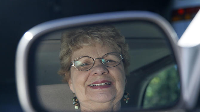 In this photo taken Sept. 12, 2012, Sandy Wiseman is reflected in the rearview mirror  in Schaumburg, Ill. Jerry Wiseman and his wife, Sandy, took refresher driving classes to help them stay safe behind the wheel for many more years. More older drivers are on the road, and they face a hodgepodge of state licensing rules that reflect scientific uncertainty and public angst over a growing question: How can we tell if it's time to give up the keys?  (AP Photo/Charles Rex Arbogast)