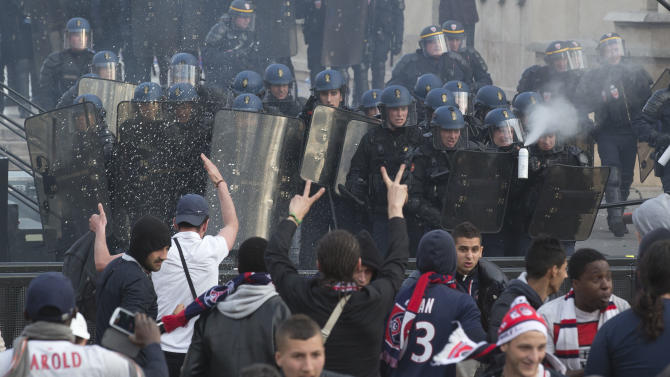 Supporters take cover from teargas, fired by riot police during the celebrations of the the French league title of Paris Saint-Germain soccer club at Trocadero Plaza in Paris, Monday, May 13, 2013. Paris Saint-Germain clinched its first French league title since 1994 by defeating Lyon 1-0 on Sunday. (AP Photo/Michel Euler)