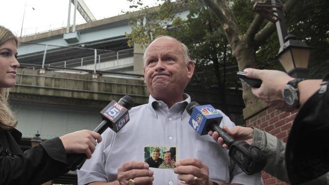 Ken Fairben holds a photo showing his son Keith, left, a victim of the Sept, 11, 2001 attacks, as he holds a press briefing on Monday, Oct. 15, 2012, outside Fort Hamilton Army base in Brooklyn, N.Y.  Military installations in New York, New Jersey, Massachusetts and Maryland are welcoming families of 9/11 victims this week to watch pretrial hearings in Cuba for five men charged in the terrorist attacks via closed-circuit television.  (AP Photo/Bebeto Matthews)