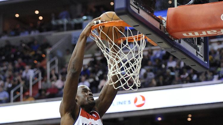 Washington Wizards center Emeka Okafor (50) dunks over Miami Heat's Terrel Harris, left, and Rashard Lewis (9) during the second half of an NBA basketball game, Tuesday, Dec. 4, 2012, in Washington. The Wizards won 105-101. (AP Photo/Nick Wass)