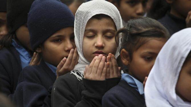 Pakistani students pray during a special ceremony for the victims of Tuesday's school attack in Peshawar, at a school in Lahore, Pakistan, Wednesday, Dec. 17, 2014. (AP Photo/K.M. Chaudary)