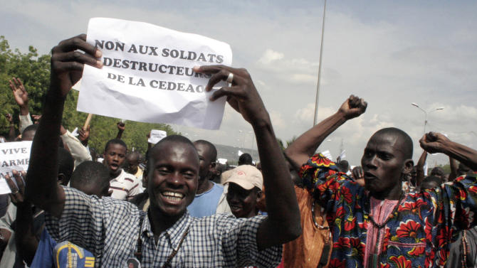 """FILE - In this Oct.18, 2012 file photo, a man carries a sign reading """"No to the destructive soldiers of ECOWAS"""" as Malians opposed to a military intervention to retake Mali's Islamist-controlled north march in the streets of the capital, Bamako, Mali. France is moving surveillance drones to western Africa amid rising concerns that an al-Qaida offshoot and its allies who control northeast Mali represent a major threat to French interests abroad and possibly at home. With six French hostages held by Islamic militants in the region, France is facing a delicate task, but has garnered support from other Western powers including the United States to keep Mali from becoming a new launchpad for global terrorism. (AP Photo/Harouna Traore, File)"""