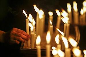 A woman places a candle after a candlelight vigil for the passengers of the missing Malaysia Airlines MH370 in central Kuala Lumpur