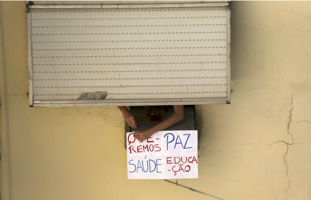 "A person hangs a sign reading, ""We want peace, health and education"", outside her window in Rio de Janeiro"