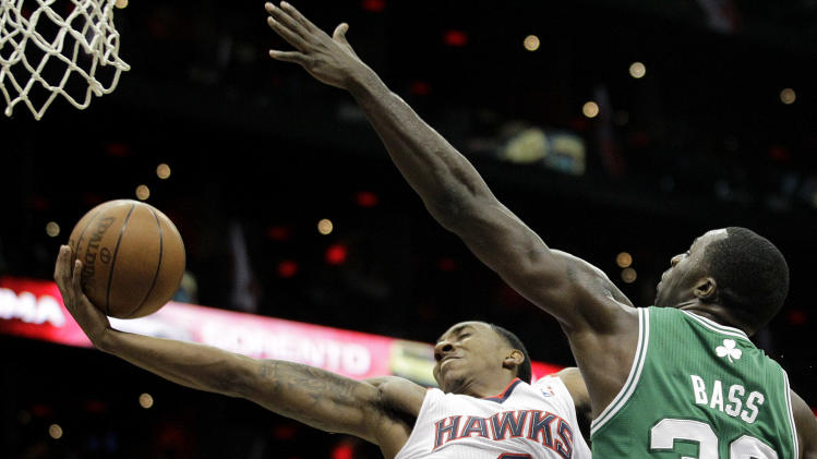Atlanta Hawks' Jeff Teague, left, puts up a shot past Boston Celtics' Brandon Bass  during the second quarter of Game 1 of an opening-round NBA basketball playoff series, Sunday, April 29, 2012, in Atlanta. (AP Photo/David Goldman)