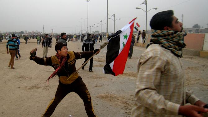 Protesters throw stones towards an Iraqi army checkpoint during clashes in Fallujah, 40 miles (65 kilometers) west of Baghdad, Iraq, Friday, Jan. 25, 2013. Iraqi troops shot dead five protesters Friday as they opened fire at stone-hurling demonstrators angry at the troops for preventing them from joining an anti-government rally west of Baghdad, officials said. (AP Photo/ Bilal Fawzi)