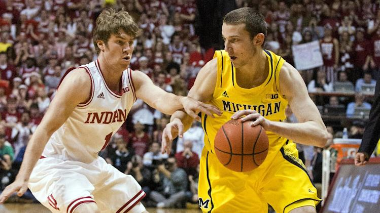 Michigan's Nik Stauskas (11) drives against Indiana's Jordan Hulls (1) during the first half of an NCAA college basketball game Saturday, Feb. 2, 2013, in Bloomington, Ind. (AP Photo/Doug McSchooler)